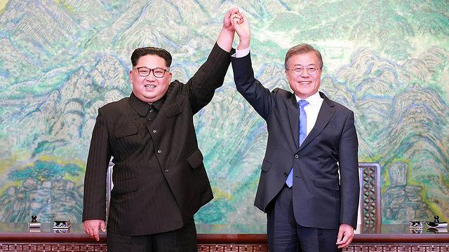 שני המנהיגים לוחצים ידיים (צילום: AFP PHOTO/KCNA VIA KNS)