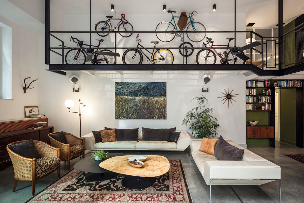 מעל פינת הישיבה, שמורכבת מכורסאות ישנות ששופצו, מספות איטלקיות וחפצים שנאספו במשך שנים, חולשים חמישה זוגות אופניים - כמספר בני המשפחה - שתלויים בקומת הגלריה (צילום: עמית גרון)