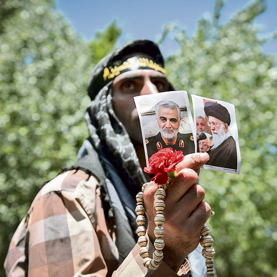 A Tehran resident holds pictures of Soleimani (L) and Khamenei. Soleimani is considered the most popular figure in Iran today  (Photo: Getty Images)