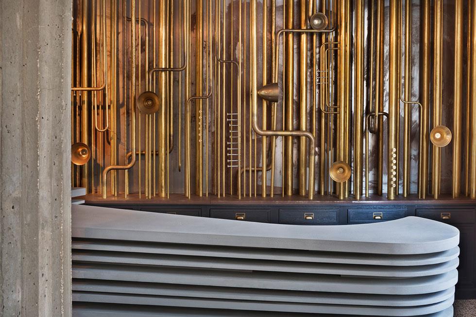 הקיר שברקע דלפק הקבלה כוסה בצינורות פליז, בהשראת כלי נשיפה (צילום: אסף פינצ׳וק)
