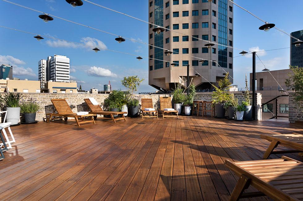 מרפסת הגג משקיפה על סביבה אינטנסיבית של מגדלים והתרחשות תל אביבית (צילום: אסף פינצ׳וק)