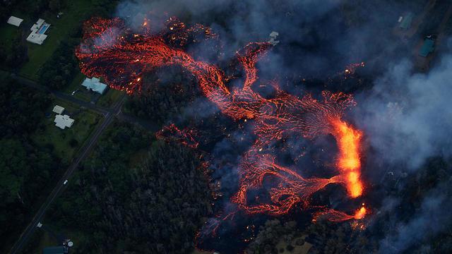 נחשול לבה מתקרב לבית בהוואי (צילום: EPA)