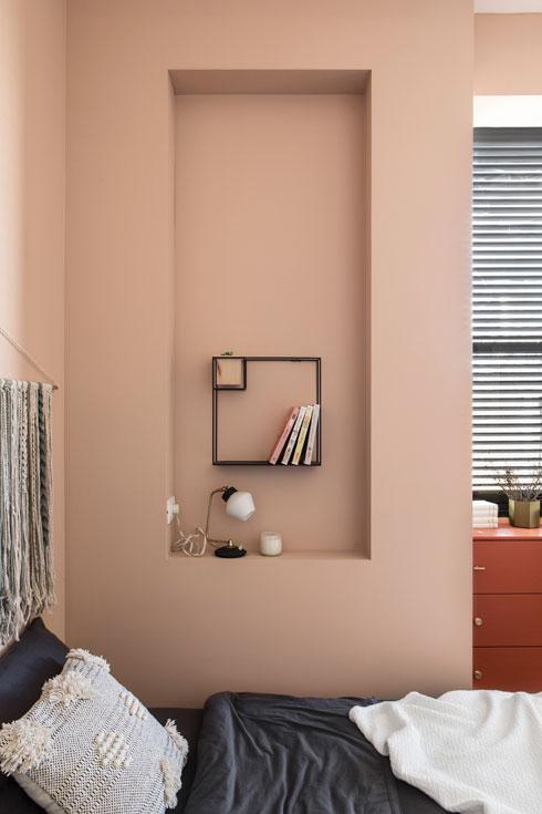 המיטה צמודה לקיר בחדר השינה ומעליה נישה לספרים ומנורה (צילום: איתי בנית)