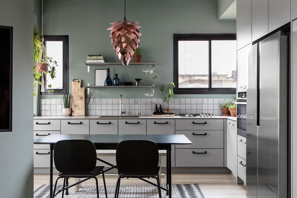 מבט מהסלון אל המטבח, שחומריו פשוטים: ארונות עם דלתות פורמייקה, אריחים לבנים רבועים ומנורה להרכבה עצמית, במחיר של כ-500 שקלים   (צילום: איתי בנית)