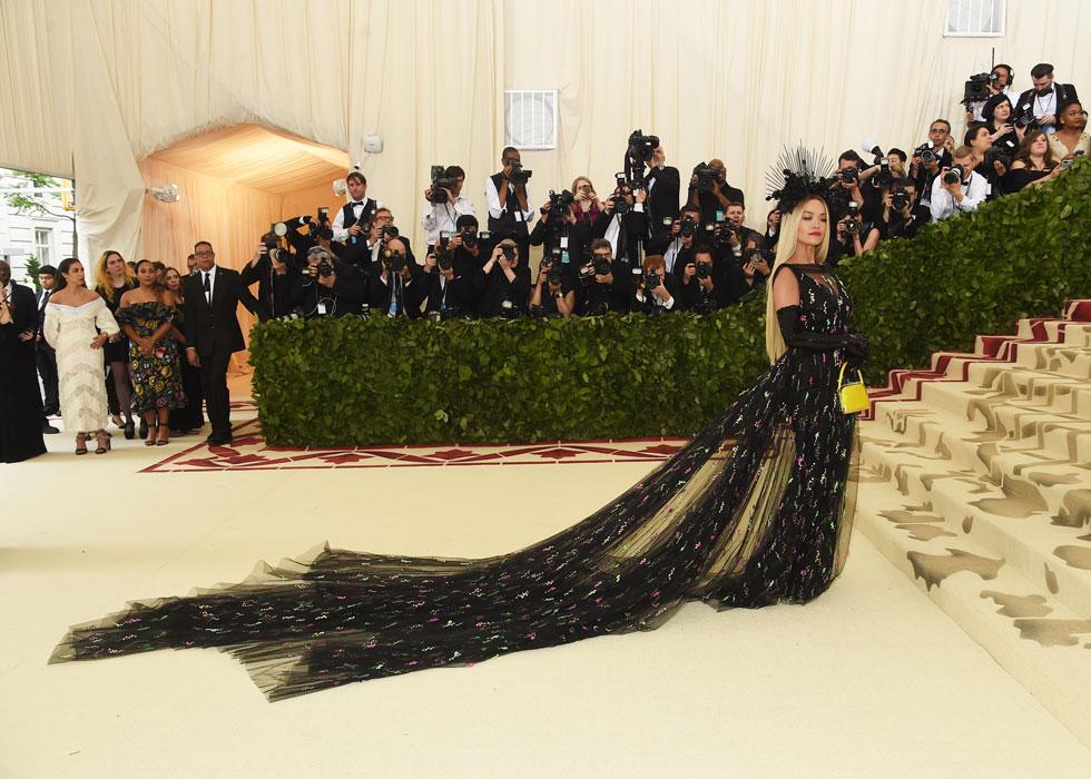 הזמרת ריטה אורה בשמלת שובל ארוכה של פראדה וטיארה שחורה במראה מריה הבתולה, משלבת בין אלמנטים נוצריים לטרנדים אביביים. את התיק הצהוב מוטב היה להשאיר בבית (צילום: Jamie McCarthy/GettyimagesIL)