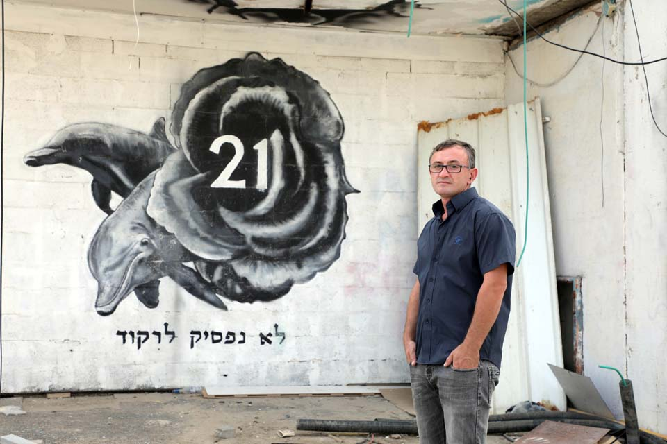 """Виктор Комоздражник у стены бывшей дискотеки """"Дольфи"""" в память о погибших. Фото: Дана Копель"""
