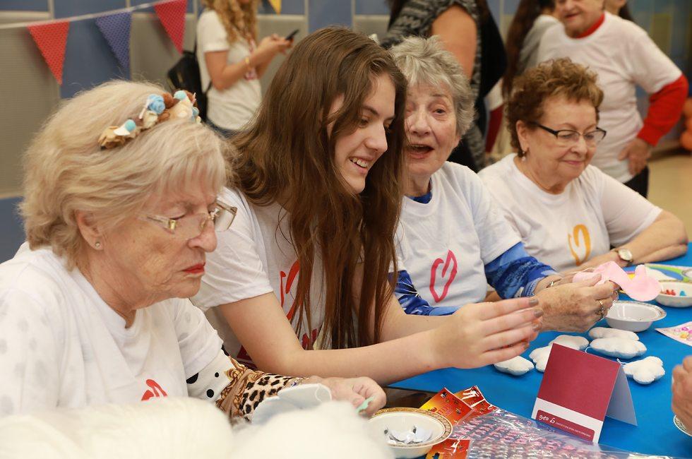 מתנדבת צעירה עושה יצירה עם שלוש קשישות ()