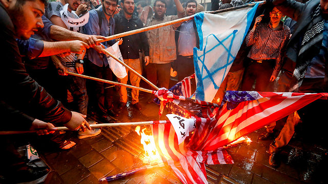 Iranian demonstrates burning Israeli and American flags   (Photo: AFP)