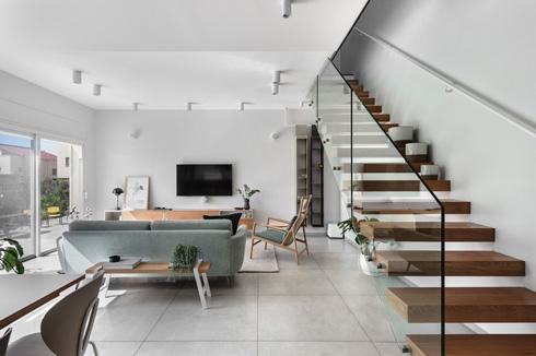 גרם מדרגות אווירי עם מעקה זכוכית העניק לסלון מראה פתוח (צילום: עודד סמדר)