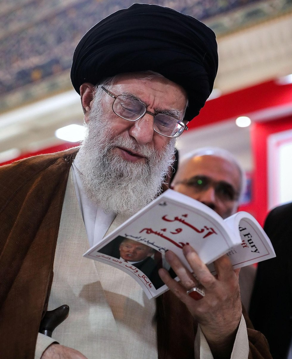 Khamenei holding a book about the US administration  (Photo: AFP)
