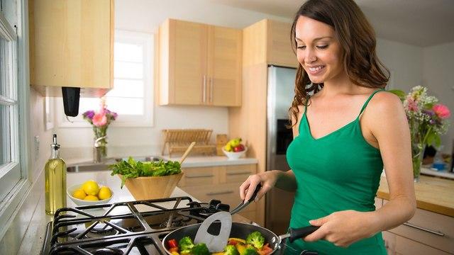 אישה מטגנת ירקות במחבת (צילום: suhtterstock)
