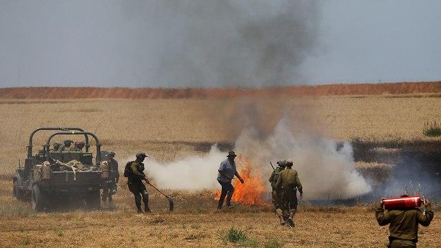 חיילים מכבים שריפה בשדה ליד קיבוץ מפלסים (צילום: רויטרס)