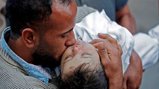 Ghandour's father holds his daughter's body  (Photo: AFP)
