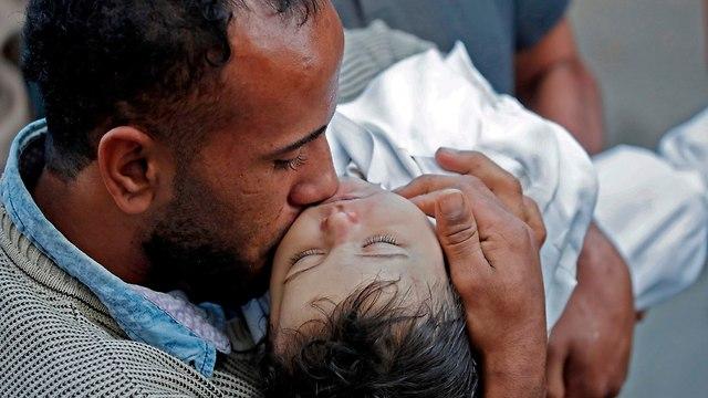 Le père de Ghandour tient le corps de sa fille (Photo: AFP)