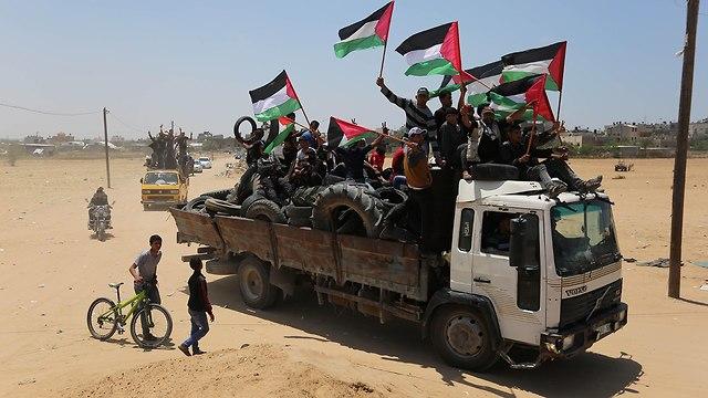 פלסטינים מביאים צמיגים ל גבול רצועת עזה כדי להבעיר אותם (צילום: MCT)