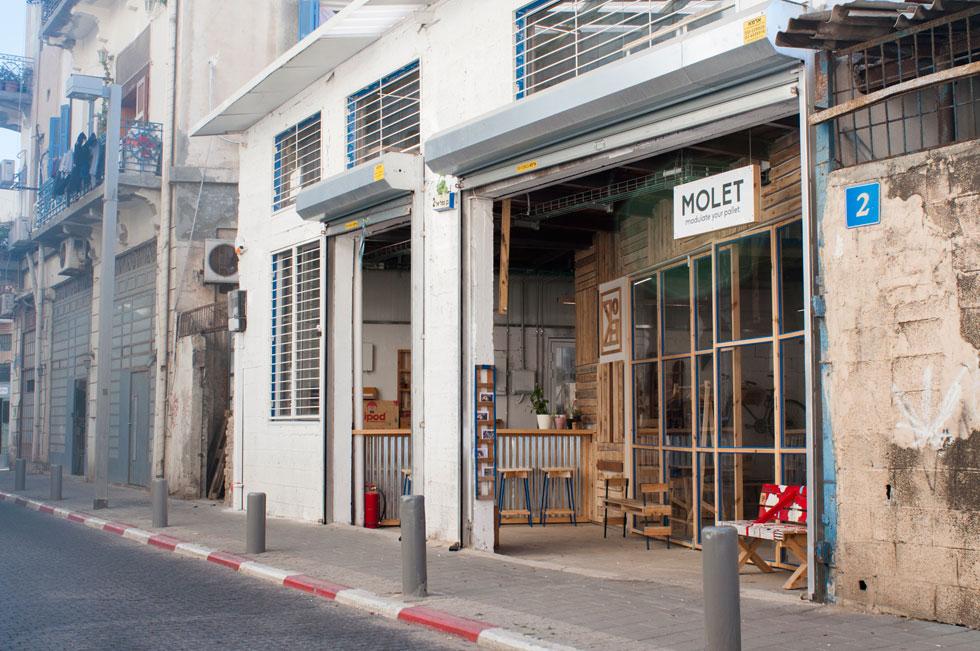 MOLET house בשוק היווני המתחדש ביפו. זהו הגלגול השלישי של הסטודיו, שהולך וגדל. המחיצות, הרצפה, החלונות והרהיטים יוצרו ברובם בעבודה עצמית - ממשטחי העמסה שנזרקו לאחר השימוש, ושאותם אספו ממחסנים ואתרי בנייה בסביבה (צילום: מולט)