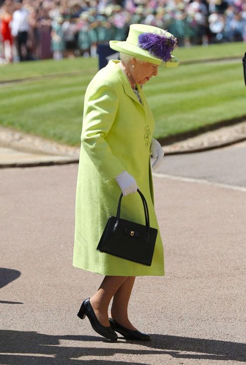 המלכה אליזבת השנייה מגיעה לחתונה במעיל מחויט בצבע ירוק ליים מעל שמלה פרחונית (צילום: GettyimagesIL)