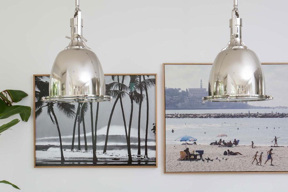 """בן הזוג חובב גלישה. על הקיר בפינת האוכל שני צילומי חוף. מימין: חוף יפו בנובמבר 2007, שנרכש בניו יורק מגעגועים לארץ. משמאל: חוף בולדווין במאווי, הוואי, ב-1969. """"הגל מאחורי הדקלים הוא גל אידאלי לגולשים"""" (צילום: הילה עידו)"""