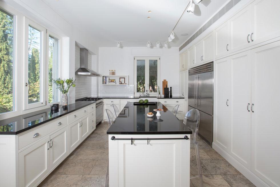 המטבח בנוי בצורת האות ח'. הארונות לבנים, המשטחים שחורים, ובמרכז אי רחב עם מקומות ישיבה. הצבע הלבן שולט בבית, כמצע נקי לכל היתר (צילום: הילה עידו)
