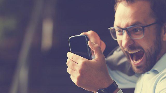 גבר מחזיק סלולרי (צילום: Shutterstock)