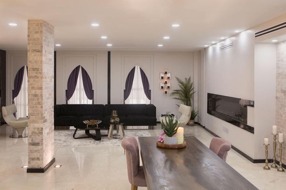 סלון האירוח המרכזי מתאפיין בפתיחות ובסגנון ערבי, עם קשתות מחודדות על פתחי החלונות. הווילונות עשויים מקטיפה. הקמין המאורך (על הקיר מימין) מוסיף יוקרה  (צילום: עמרי טלמור)