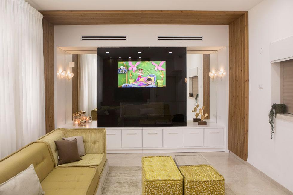 חדר המשפחה הוא הנעים והחמים ביותר מבין הסלונים, והאהוב על בני הבית. הוא מלא בספות ובקוביות מרופדות, שהילדים אוהבים לשכב עליהן כשהם צופים במסך הטלויזיה הענק. פסלון הצבר המוזהב (מימין) נרכש בגלריה בשפרעם  (צילום: עמרי טלמור)