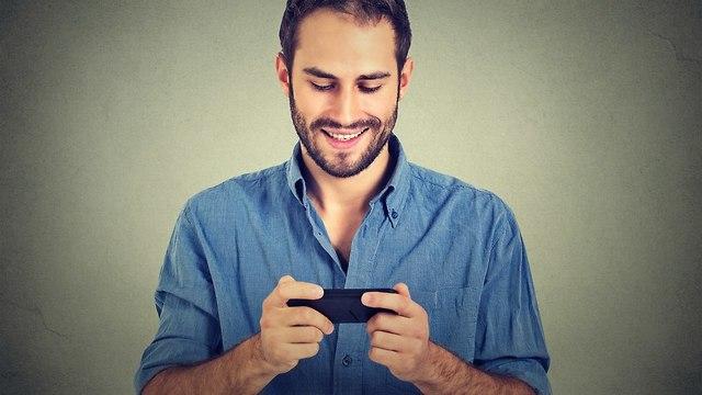 גבר מציץ בסמארטפון שלו (צילום: Shutterstock)