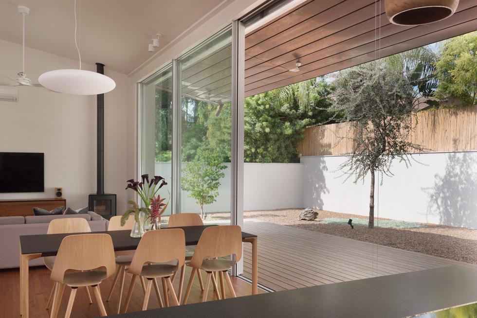 """מרחב המגורים פתוח אל החצר האחורית, שעוצבה עם דק, חלוקי נחל קטנטנים וארבעה עצי אלון. הפונקציות השונות - מטבח, פינת אוכל, סלון - מסודרות ברצף. """"רצינו פשטות, בית במפלס אחד"""", אומרת בעלת הבית. חלוקת העבודה הייתה ברורה: האדריכליות על התכנון, בני הזוג על בחירת החומרים והרהיטים (צילום: גלית דויטש)"""