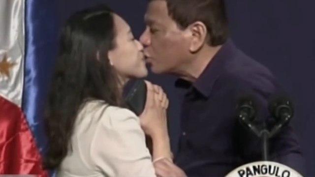 נשיא הפיליפינים רודריגו דוטרטה מנשק עובדת על הבמה ב דרום קוריאה ()