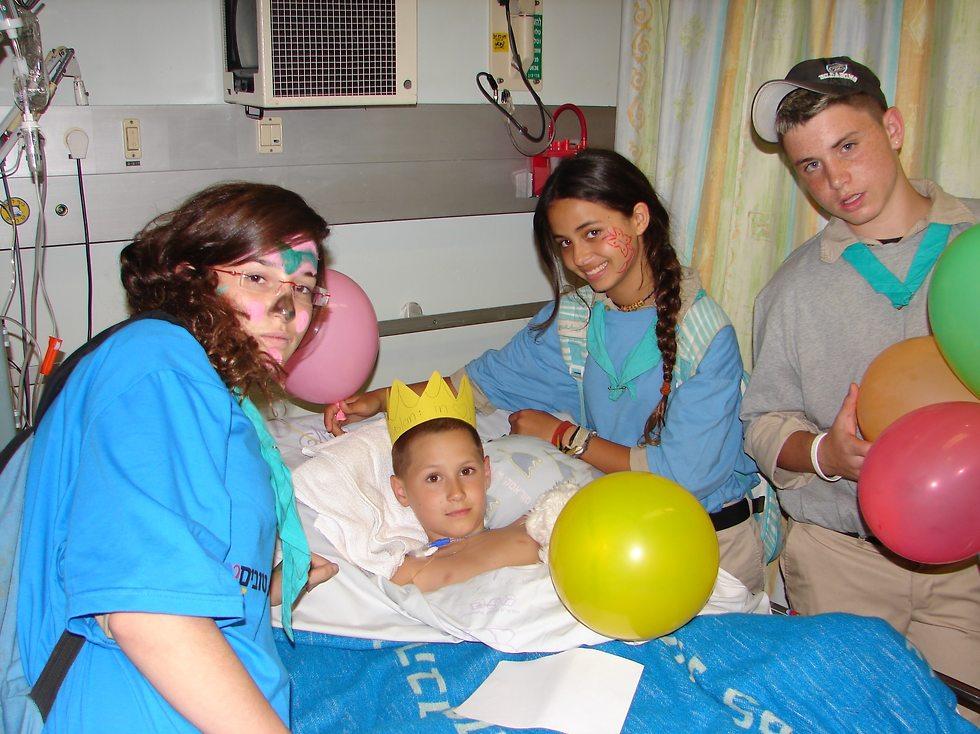 מתנדבים סביב ילד במיטת בית חולים ()