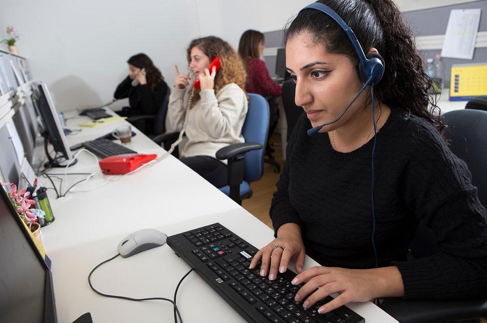 צעירה מקלידה על מחשב עם אוזניות ורמקול מחוברים אליה - מוקדנית ()