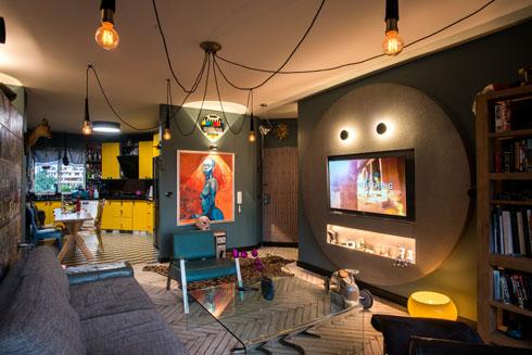 קיר טלוויזיה עגול ומנצנץ בסלון, בסגנון שנות ה-70. כל חלל בדירה זכה ל''אישיות'' משלו (צילום: שחר שדרין - SHEDRIN STUDIO)