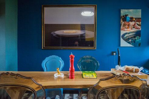 שולחן האוכל עשוי מעץ מבוקע. הכסאות - פלסטיק צבעוני בסגנון בארוקי (צילום: שחר שדרין - SHEDRIN STUDIO)