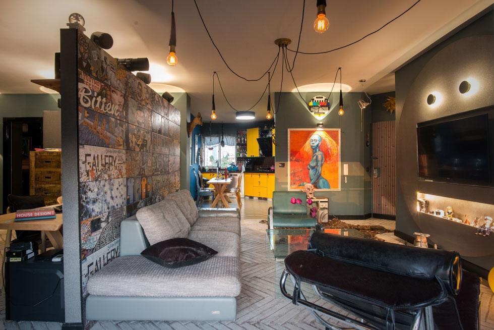 מצד אחד של מחיצת האריחים המודפסים הסלון עם מסך טלוויזיה ממוסגר בקיר עגול, ומצדה השני - הסטודיו הביתי. הספה בסלון איטלקית, השז-לונג של לה-קורבוזיה  (צילום: שחר שדרין - SHEDRIN STUDIO)