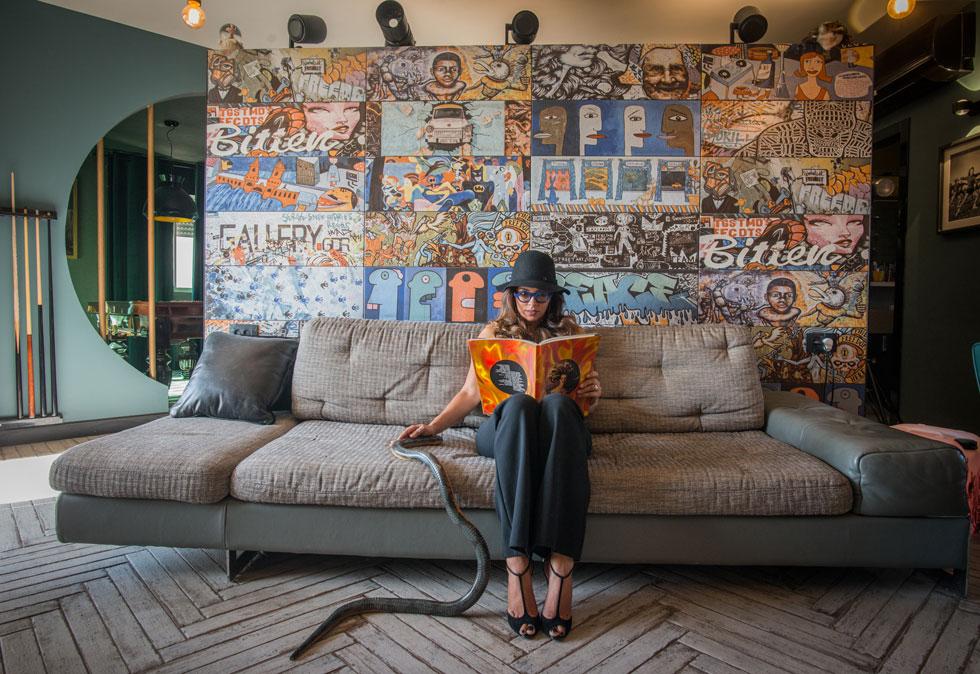 """האדריכלית פלביה גרסיה-בן זאב מדגמנת ישיבה על ספת הסלון. """"בהתחלה היה קצת בלבול"""", אומר בעל הדירה, שחר שדרין. """"המחיצה היתה אמורה להפריד אזור משחק לילדים. אבל החלטתי לעבוד מהבית, ומאחורי המחיצה מיקמנו את הסטודיו""""   (צילום: שחר שדרין - SHEDRIN STUDIO)"""