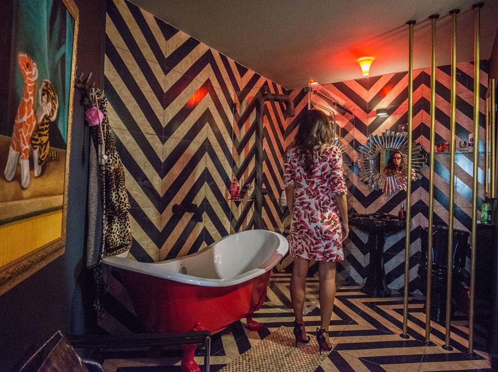 חדר הרחצה אינו מופרד מאזור השינה. הריצוף ממשיך על הקירות הרטובים, והאסלה השחורה מבריקה מופרדת רק באופן מרומז, באמצעות מוטות מוזהבים. עמוד המקלחת הצומח מהרצפה (משמאל) נראה מאסיבי, כמעט אגרסיבי  (צילום: שחר שדרין - SHEDRIN STUDIO)
