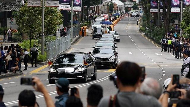 קהל צופה בשיירתו של שליט צפון קוריאה קים ג'ונג און בדרכו לפסגה עם טראמפ בסינגפור (צילום: EPA  )