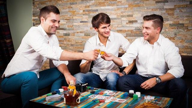 חבורת גברים משחקים פוקר בסלון (צילום: Shutterstock)