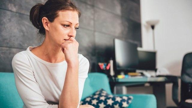 אישה יושבת ומשדרת תחושה של מצוקה (צילום: Shutterstock)