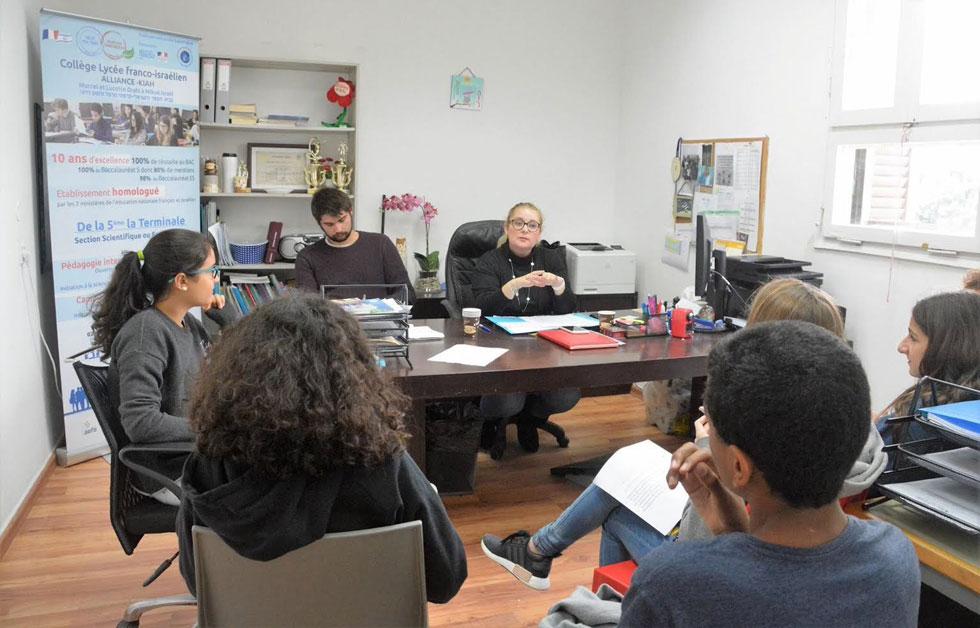"""גאסשה (מאחורי השולחן, מצד שמאל) בישיבה בבית הספר במקווה ישראל. """"גיליתי שאני אוהב ללמד"""" (צילום: באדיבות התוכנית הבינלאומית האגודה להתנדבות)"""
