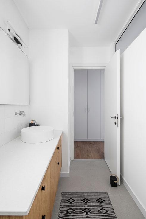 גם בחדר הרחצה הבחירה באריחים לבנים ריבועיים לכל גובה הקיר מעניקה לחלל המוארך תחושת מרחב וניקיון (צילום: איתי בנית)