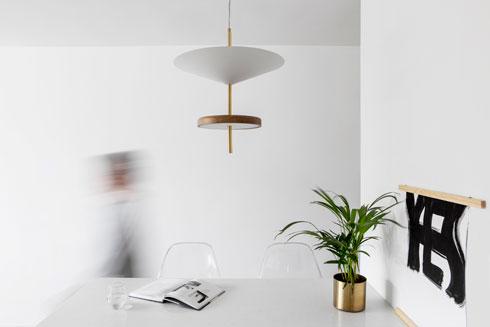 המנורה מעל פינת האוכל עוצבה בצורת שתי צלחות מרחפות. האור בוקע מהחלק התחתון של צלחת העץ (צילום: איתי בנית)