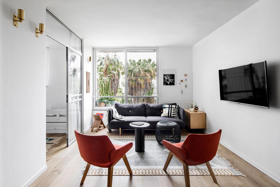 מעטפת הדירה נקייה ולבנה, כבמה לגופי התאורה שמעצב אסף וינברום. רהיטי הסלון מוסיפים מעט צבע, וספוטים קטנים מפליז מחליפים את מנורת התקרה המקובלת ומפיקים אור שחוזר מהקיר, רך ועדין יותר (צילום: איתי בנית)