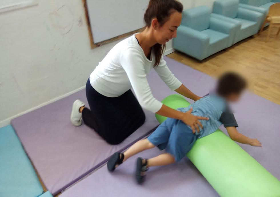 """בורדייה עם אחד הילדים שבהם טיפלה. """"חשבתי שצועקים עליי כי אני עושה משהו לא בסדר"""" (צילום: באדיבות התוכנית הבינלאומית האגודה להתנדבות)"""