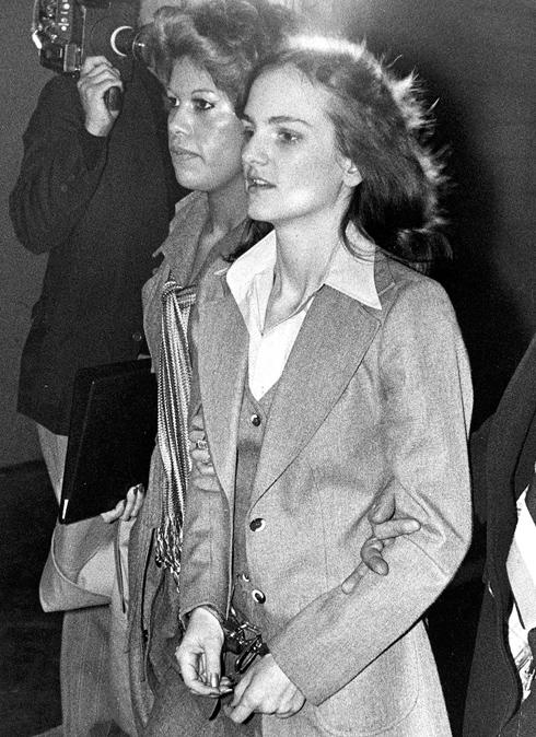 יורשת המיליונים פטי הרסט הפכה מקורבן חטיפה לפושעת נודעת, בעקבות שוד בנק שביצעה באפריל 1974. בתמונות מתוך השוד רואים את הרסט מחזיקה רובה סער ומערכת לבוש של עוד יום בעבודה: מכנסיים שחורים, סריג אפור ומעיל טרנץ'  (צילום: AP)