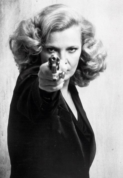 """היא אומנם פושעת שחזרה למוטב וזוגתו לשעבר של ראש המאפיה, אבל ג'ינה רולנדס בתפקיד """"גלוריה"""" של ג'ון קאסווטס מ-1980, היא אחת הדמויות האופנתיות ביותר בסרטי מאפיה. בסרט המסע הזה מציגה גלוריה חזות נשית ורכה כאנטיתזה לעברה, בזכות חצאיות מידי בגזרות קלוש וז'קטים קלילים ממשי ופוליאסטר, שמתחתם מבצבצות גופיות צבעוניות, כשבידה האחת מזוודה וילד צעיר, ובידה השנייה אקדח טעון שהיא לא מהססת לעשות בו שימוש (צילום: rex/asap creative)"""
