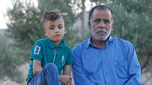 Hussein Dawabsheh with his grandson Ahmed, the only one to survive the attack (Photo: Shaul Golan)