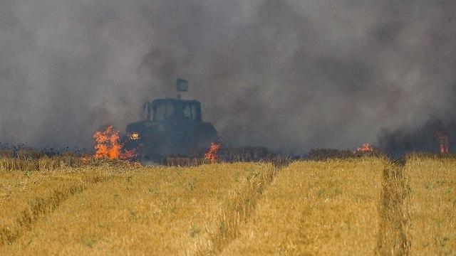 טרקטור בשדה בוער בעוטף עזה (צילום: AP)