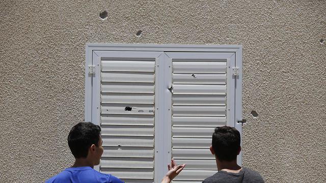 זוג אזרחים בודקים את הנזק שנגרם מירי רקטות על עוטף עזה (צילום: EPA)