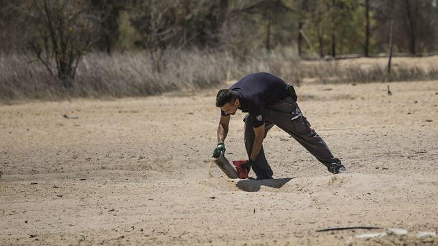 חבלני משטרה אוספים רסיסי רקטה (צילום: EPA)